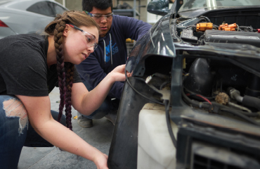 Woman and man working on a car