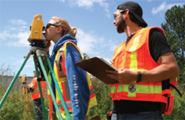 Two people using surveying equipment