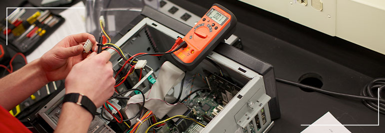 Person checking the power supply of a computer using a multimeter